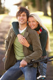 Portrait Of Young Couple With Cycle In Autumn Park Stock Photography