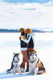 Portrait of young couple with dogs smiling and hugging in winter stock image