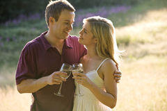 Portrait of a young couple drinking wine, looking at each other lovingly Stock Photos