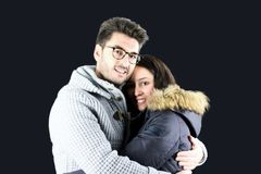 Portrait of young couple embraced in winter clothes. Black background Stock Photos