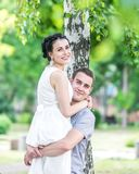 Portrait of young couple female bride and male bridegroom hugging in summer park. Man husband raised woman wife and both looking i. Portrait of young couple Royalty Free Stock Images