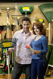 Portrait of young couple with gardening claw in store Royalty Free Stock Photo