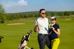Young women and men playing golf at sunny day royalty free stock photo