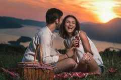 Portrait of young couple having good times on a picnic date. Behind them is a beautiful sunset over Boka Bay royalty free stock photos