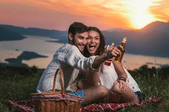 Portrait of young couple having good times on a picnic date. Behind them is a beautiful sunset over Boka Bay stock photo