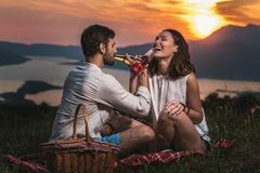 Portrait of young couple having good times on a picnic date. Behind them is a beautiful sunset over Boka Bay royalty free stock image