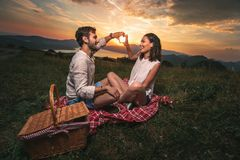 Portrait of young couple having good times on a picnic date. Behind them is a beautiful sunset over Boka Bay stock photos