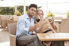 Portrait of young couple having red wine at outdoor restaurant Royalty Free Stock Photography