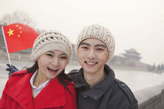 Portrait of young couple holding Chinese flag outdoors in wintertime, Beijing Stock Photography