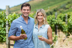 Portrait of young couple holding wine bottle and glass Royalty Free Stock Photos