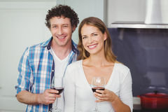 Portrait of young couple holding wineglasses in kitchen. Portrait of smiling young couple holding wineglasses in kitchen at home stock photography