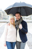 Portrait of a young couple on holidays under the rain Stock Photo
