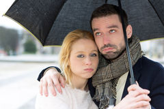 Portrait of a young couple on holidays under the rain Stock Image