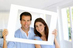 Portrait of young couple at home holding a frame Royalty Free Stock Images