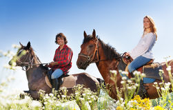 Portrait of young couple horseback riding. Side view portrait of smiling young couple horseback riding on purebred horses in flowery meadows Royalty Free Stock Photography