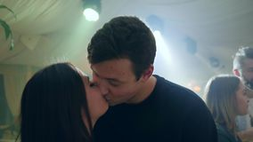 Portrait of young couple kissing in intimate atmosphere on background of bright lights in club stock footage