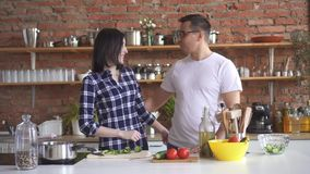 Portrait of a young couple in the kitchen,girl cuts vegetables and gives a man a try stock video