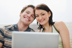 Portrait of young couple with laptop. At living room Royalty Free Stock Photos
