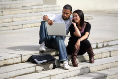 Portrait of a young couple with laptop. Mixed-race man with an asian woman sitting on steps with a laptop Stock Image