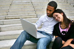Portrait of a young couple with laptop. Mixed-race man with an asian woman sitting on steps with a laptop Royalty Free Stock Image