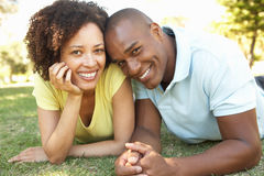 Portrait Of Young Couple Laying On Grass In Park Royalty Free Stock Image