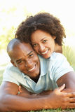 Portrait Of Young Couple Laying On Grass In Park Royalty Free Stock Photo