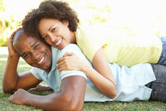 Portrait Of Young Couple Laying On Grass In Park Stock Images