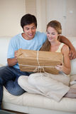 Portrait of a young couple looking at a package Stock Photos