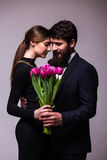 Portrait of young couple in love with bouquet of lila tulips posing dressed in classic clothes on grey backround. Royalty Free Stock Image