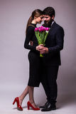 Portrait of young couple in love with bouquet of lila tulips posing dressed in classic clothes on grey backround. Stock Photography