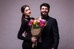 Portrait of young couple in love with bouquet of spring tulips posing dressed in classic clothes on grey backround. Royalty Free Stock Image