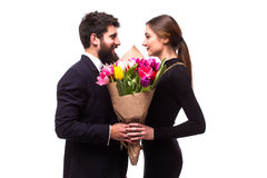 Portrait of young couple in love with bouquet of spring tulips posing dressed in classic clothes on white backround. Stock Images