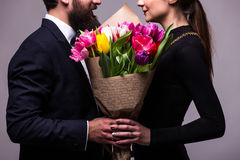 Portrait of young couple in love with flowers tulips posing at studio dressed in classic clothes on grey backround. Stock Image