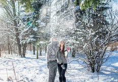 Portrait of young couple in love with lollipop throwing snow Royalty Free Stock Images
