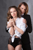 Portrait of young couple in love posing at studio dressed in classic clothes Royalty Free Stock Photos