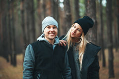 Portrait of young couple in love walking in beautiful forest enjoying hugging and smiling. Stock Photos