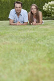 Portrait of young couple lying side by side on grass in park Royalty Free Stock Photography
