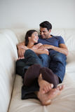 Portrait of a young couple lying on a sofa Royalty Free Stock Images