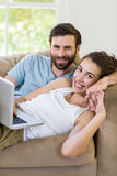 Portrait of young couple lying on sofa and using laptop Stock Photography