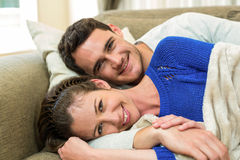 Portrait of young couple lying together on sofa Stock Photo