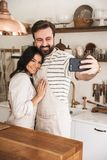 Portrait of young couple man and woman 30s wearing aprons taking selfie photo while cooking at home. Portrait of young couple men and women 30s wearing aprons stock image