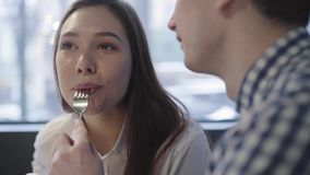 Portrait of young couple in modern cafe enjoying time together close up. Unrecognizable man feeding his girlfriend. Sitting in modern cafe. Pretty woman smiling stock video