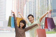 Portrait of young couple posing with shopping bags in hands, Beijing, China Royalty Free Stock Image