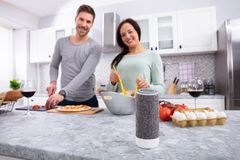 Portrait Of Young Couple Preparing Food In Kitchen stock photo