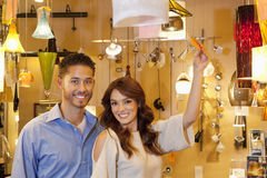 Portrait of young couple with price tag in lights store Royalty Free Stock Images