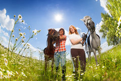 Portrait of young couple with purebred horses Royalty Free Stock Photography