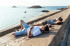 Portrait of young couple relaxing lying on the walls. Facing the sun. Saint Malo, Brittany, France, Europe stock photo