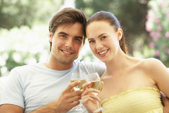 Portrait Of Young Couple Relaxing On Sofa Drinking Wine Together Royalty Free Stock Photography