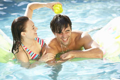 Portrait Of Young Couple Relaxing In Swimming Pool Stock Photography