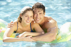 Portrait Of Young Couple Relaxing In Swimming Pool Stock Photo